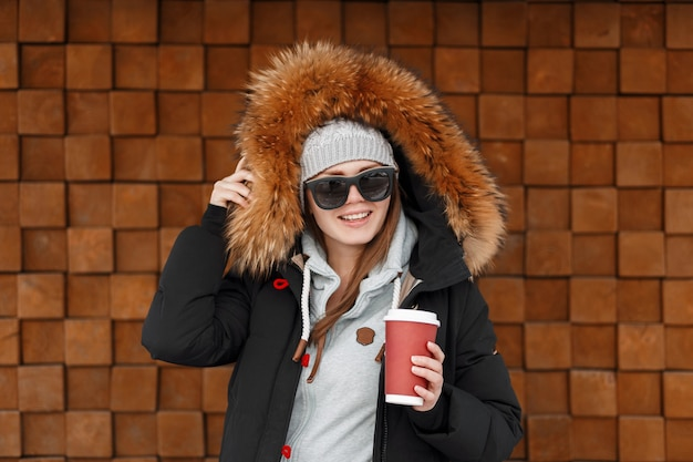 Cheerful young hipster woman in vintage knitted hat in sunglasses in a winter jacket with fur is standing and holding in her hands a red cup with hot coffee near a wooden wall. happy joyful girl.