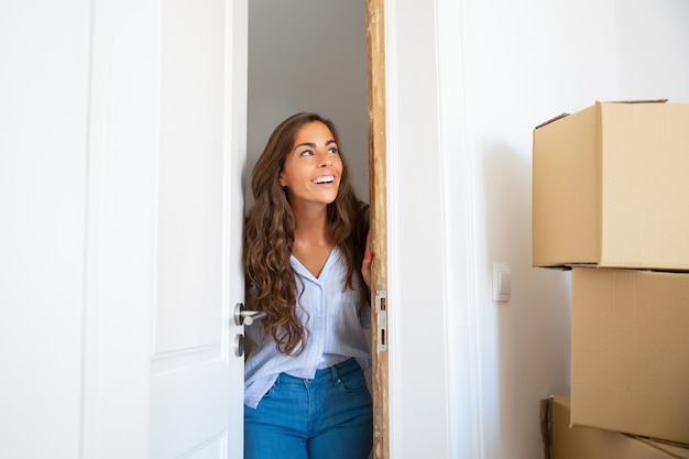 Cheerful young hispanic woman moving into new apartment, opening door, standing in doorway, looking at stack of carton boxes and smiling