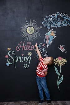 Cheerful young kid standing and pointing at the hello spring
