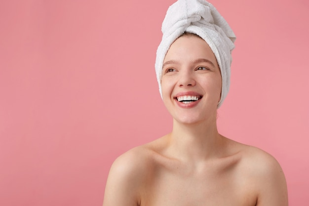 Cheerful young lady after shower with a towel on her head, broadly smiles, looks away, feels so happy, stands.