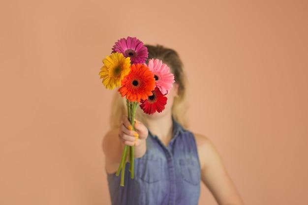 陽気な若い女性と花のカモミールを手に。カモミールのブーゲットと立っている美しい魅力的な女性。 Premium写真
