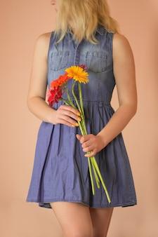 陽気な若い女性と花のカモミールを手に。カモミールのブーゲットと立っている美しい魅力的な女性。