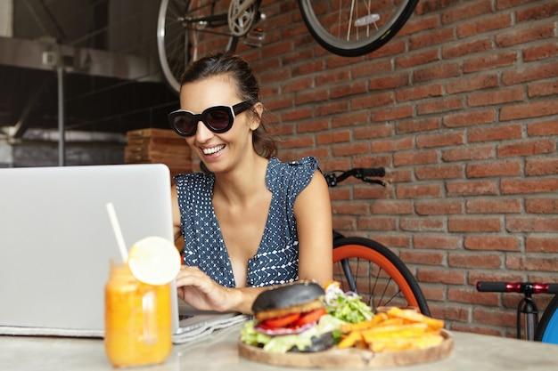 ラップトップコンピューターの前に座っている色合いで陽気な若い女性