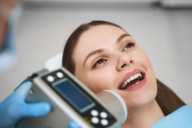 Cheerful young lady is being treated at dentist with special electronical equipment for perfect smile