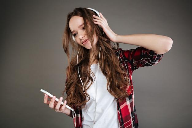 Musica d'ascolto della giovane signora allegra con le cuffie