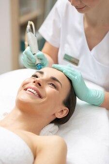 전문 미용사가 특별한 도구를 사용하고 그녀의 얼굴 피부에 영양을 공급하면서 쾌활한 젊은 아가씨가 행복하고 웃고 있습니다.