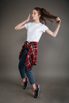 Cheerful young lady posing and dancing. looking aside.
