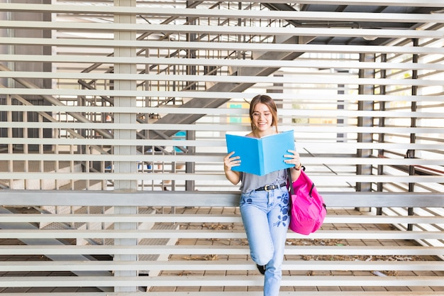 Cheerful young lady reading book near wall