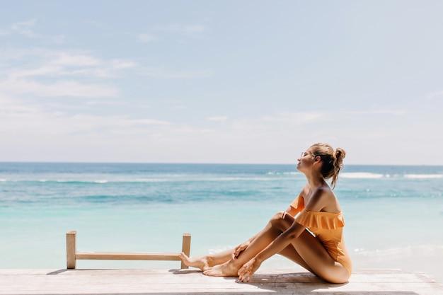 Giovane signora allegra che si siede sulla spiaggia nella mattina d'estate. colpo esterno della splendida ragazza in costume da bagno arancione in posa in spiaggia