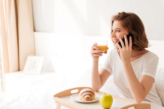 Cheerful young lady sitting indoors with croissant drinking juice
