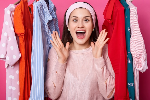 Cheerful young lady spreads palms near face and shouts hooray. positive woman likes new outfit. beautiful girl with toothy smile stands between fashion clothes. female bursts out from good feelings.