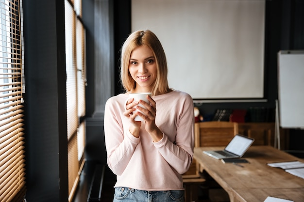 Cheerful young lady standing in cafe drinking coffee