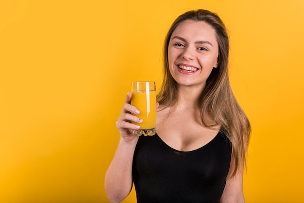 Cheerful young lady with glass of juice