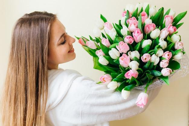 Жизнерадостная девушка с длинными волосами возбуждается, чтобы получить букет розовых тюльпанов в женский день