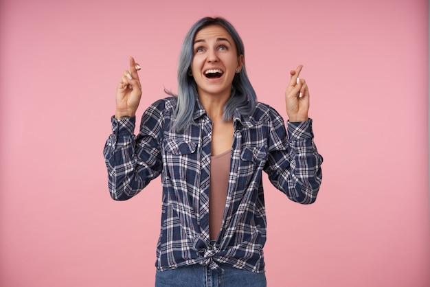 교차 손가락으로 손을 올리고 분홍색에 고립 된 열린 입으로 즐겁게 위쪽으로 보는 자연스러운 메이크업으로 쾌활한 젊은 아가씨