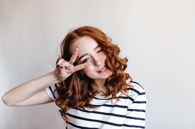 창백한 피부와 평화 기호 포즈 붉은 머리를 가진 쾌활 한 젊은 아가씨. 고립 된 스트라이프 티셔츠에 놀라운 소녀입니다.