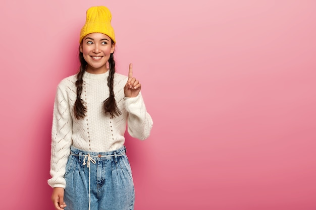 Cheerful young lady with two plaits, raises finger above, promots top copy space against pink background