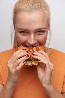 Allegro giovane bella donna bionda con il manicure bordeaux morde voracemente hamburger e guarda con gioia la telecamera, vestita di maglietta arancione mentre si trova su sfondo bianco