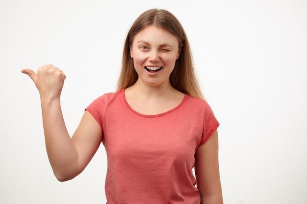 陽気な若い素敵な金髪の長い髪の女性は、白い背景の上に分離された、上げられた手で脇に見せながら、カメラでウインクと幸せな笑みを浮かべて