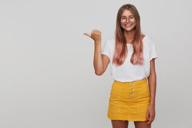 쾌활한 젊은 사랑스러운 금발의 여자가 흰색 벽 위에 서있는 동안 안경을 착용하고 엄지 손가락으로 옆으로 보이고 널리 웃고있는 동안 자연스러운 화장과 함께