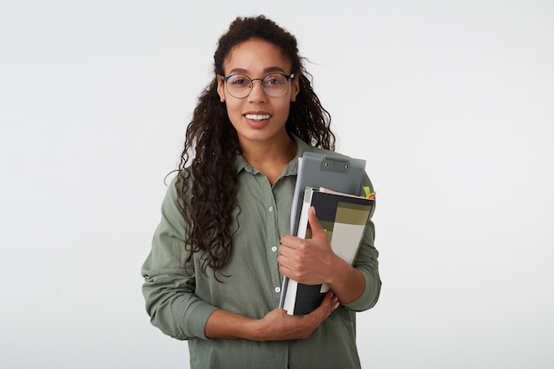 Cheerful young lovely brown haired curly female with dark skin holding books while looking gladly at camera with broad smile, isolated over white background