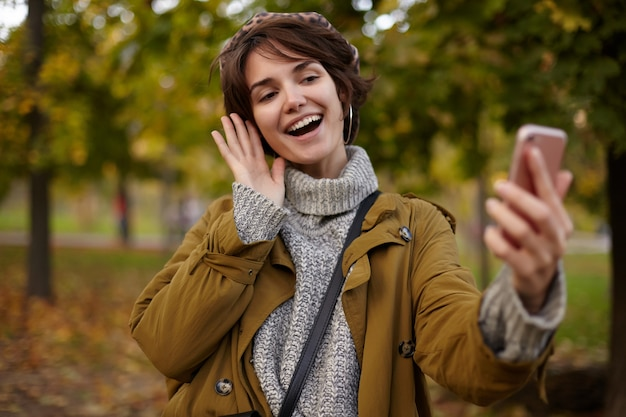 Cheerful young lovely brown haired female with casual hairstyle raising hand with mobile phone while making photo of herself, smiling widely while posing over yellowed trees