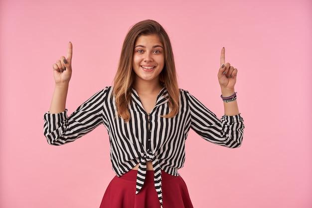 ピンクの上に立っている間、縞模様のシャツと赤いスカートを着て、隆起した人差し指で上向きに、心地よく笑っている陽気な若い素敵な茶色の髪の女性