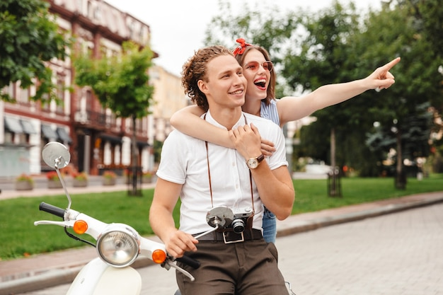 Cheerful young lovely couple posing together with retro scooter while looking away outdoors