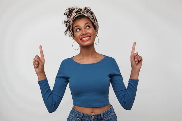 Allegro giovane bella donna bruna riccia con acconciatura casual mantenendo gli indici sollevati mentre punta verso l'alto e sorride volentieri, posa su sfondo bianco