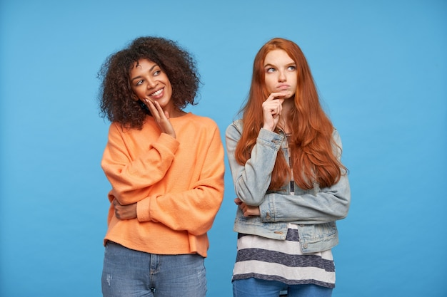 Cheerful young lovely curly dark skinned brunette lady holding raised hand on her cheek while smiling widely, standing over blue wall with pensive redhead long haired female