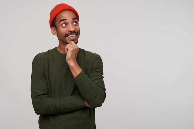 白い上に立っている間、彼のあごに手を保ち、心地よく微笑んで、赤い帽子とカーキ色のセーターを着て、黒い肌を持つ陽気な若い素敵な黒髪のひげを生やした男性