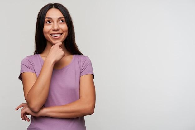 カジュアルな髪型の陽気な若い素敵な黒髪の女性は、白でポーズをとっている間、手を上げて彼女のあごを持って、幸せそうに横を見て、広く笑っています