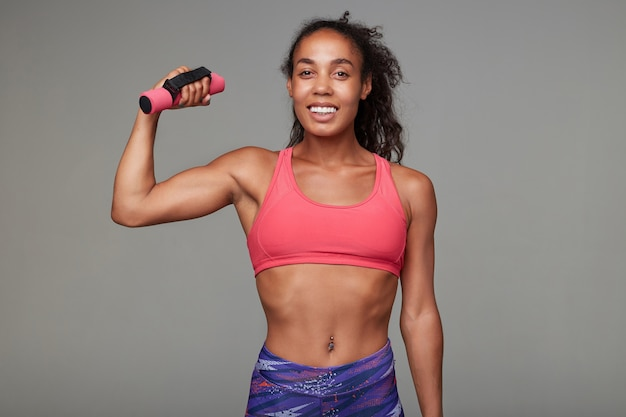 Cheerful young lovely dark skinned brunette sportswoman in athletic wear looking happily and raising hand with dumbbell while posing
