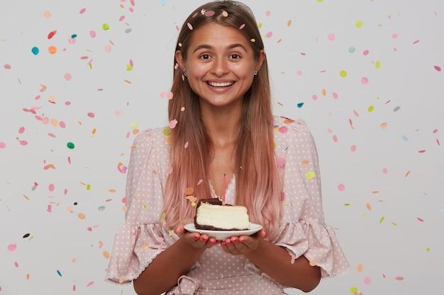 バースデーケーキとプレートを保持し、白い壁に隔離された広い笑顔で幸せそうに見える薄茶色の長い髪の陽気な若い素敵な女性