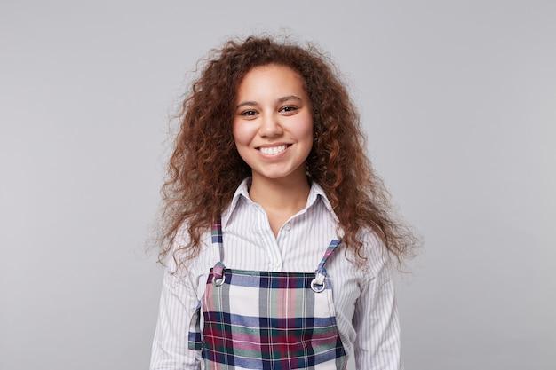 Веселая молодая милая длинноволосая кудрявая брюнетка женщина показывает свои белые идеальные зубы, счастливо улыбаясь, стоя на сером