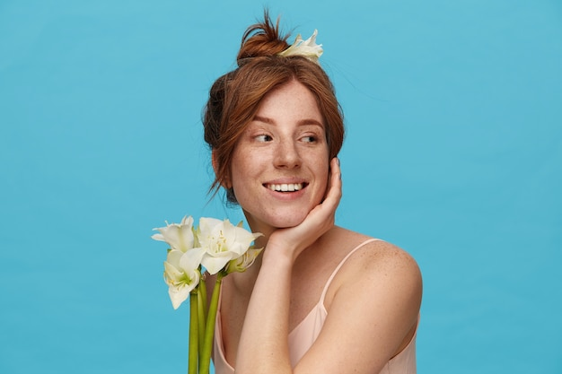 Cheerful young lovely redhead female leaning her head on raised hand and looking positively aside with pleasant smile, standing over blue background with flowers