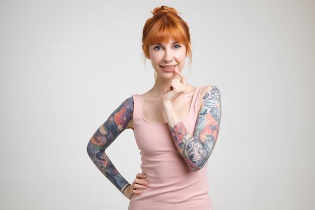 ヌードシャツの白い背景に立って、魅力的な笑顔でカメラを積極的に見て鼻ピアスと陽気な若い素敵な赤毛の入れ墨の女性