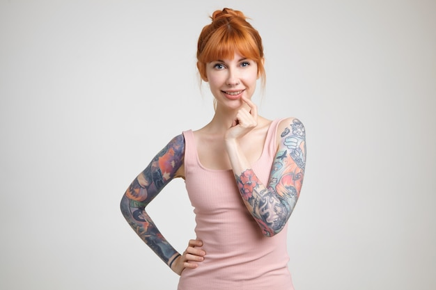 Cheerful young lovely redhead tattooed lady with nose piercing looking positively at camera with charming smile, standing against white background in nude shirt