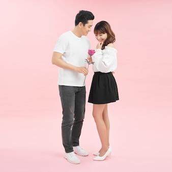 バラを持って、顔を合わせて立ってピンクの背景で隔離しながら笑顔の陽気な若い愛情のあるカップル