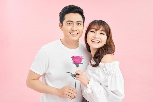 彼女の手に赤いバラを持っている女性が互いに近くに立っている陽気な若い愛情のあるカップル