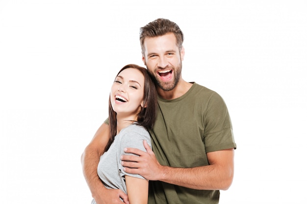 Cheerful young loving couple standing isolated
