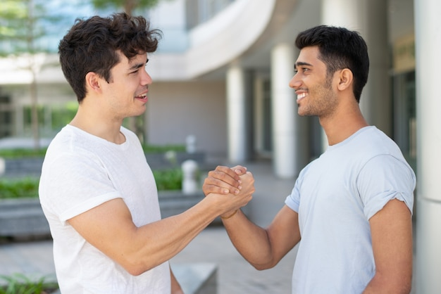 Cheerful young male friends meeting and greeting with handshake