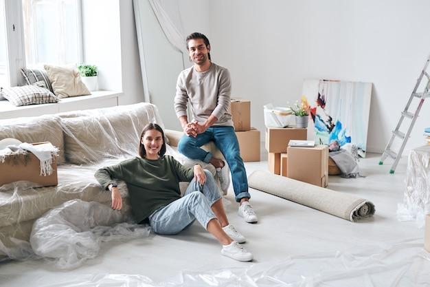 Веселый молодой мужчина и женщина в джинсах и пуловерах сидят на диване в гостиной своего нового дома или квартиры после снятия