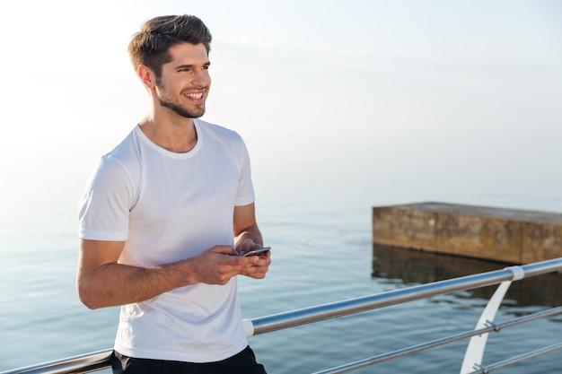 海の近くに立っている携帯電話を使用して白いtシャツを着た陽気な青年アスリート