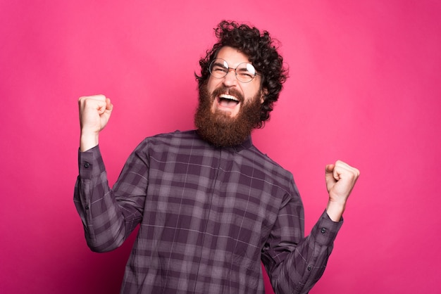 Веселый молодой человек взволнован, кричит и держит обе руки вверх