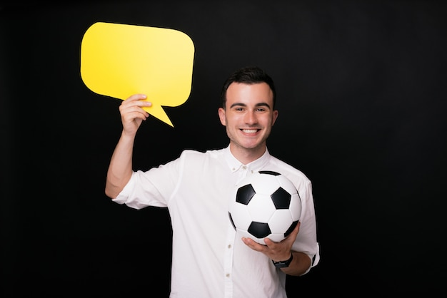 Cheerful young man on black background holding a soccer or football ball and a yellow speech bubble. thoughts about sports.