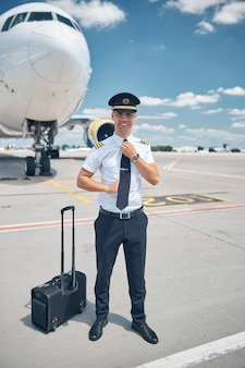 Cheerful young man in captain hat fixing his tie and smiling while standing in airfield with airplane and sky on background