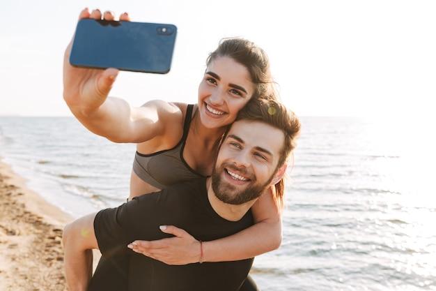 Веселый молодой человек, несущий свою девушку на спине