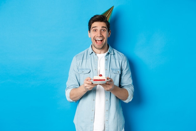 파티 모자를 쓰고 생일을 축하하는 쾌활한 청년, b-day 케이크를 들고 파란색 배경에 서서