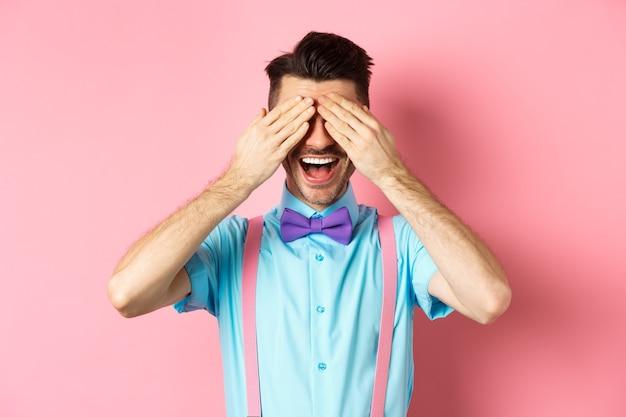 쾌활 한 젊은 남자 축 하, 닫힌 된 눈과 행복 한 미소로 놀람을 기다리고, 분홍색 배경에 즐거운 서.